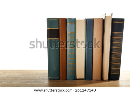Old books on wooden table isolated on white - stock photo