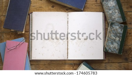 old books, one opened, with blank pages on wooden background