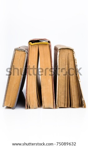 Old books piled together over white background - stock photo