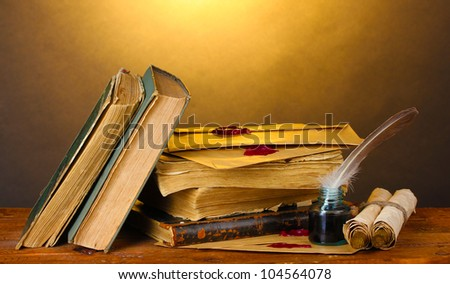 old books, scrolls, feather pen and inkwell on wooden table on brown background - stock photo
