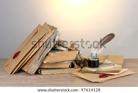 old books, scrolls, feather pen and inkwell on wooden table on grey background