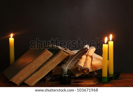 old books, scrolls, feather pen inkwell and candles on wooden table on brown background - stock photo