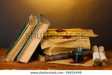 old books, scrolls, ink pen and inkwell on wooden table on brown background - stock photo