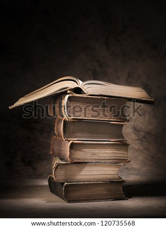 Old books stacked, with one open book on top. - stock photo