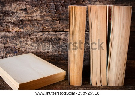 old books standing in a row next to the book on a wooden table - stock photo