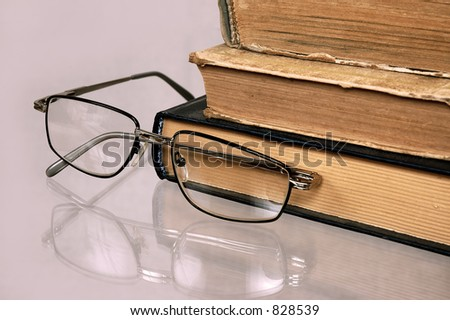 Old books with glasses lay on a table.