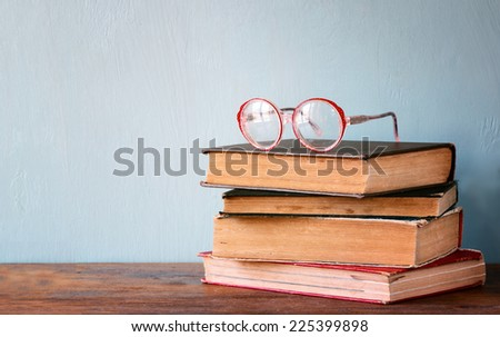 Old books with vintage glasses on a wooden table. retro filtered image  - stock photo
