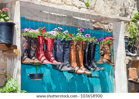 Old boots used as flower pots on the entrance door of a house, Israel - stock photo