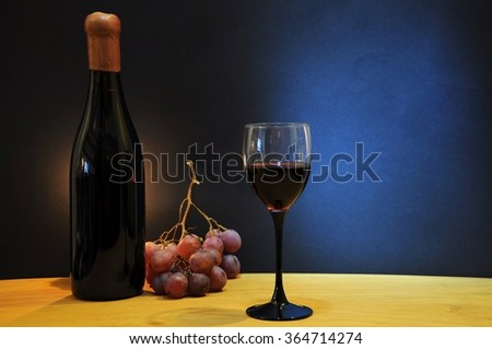 Old bottle of esteemed italian wine with glass and grapes on wooden table - stock photo