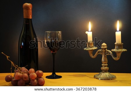 Old bottle of esteemed italian wine with glass, candlestick and grapes - stock photo