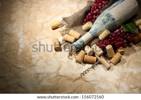 Old bottle of wine, grapes and corks on old paper background - stock photo