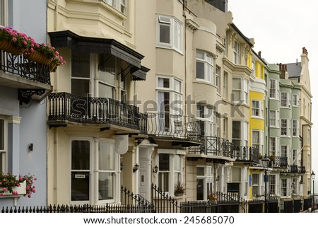 old bow windows at Brighton,  foreshortening of bow windows on facades of old houses on an uphill street in touristic sea town,  Brighton, East Sussex  - stock photo