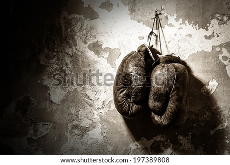 old boxing gloves hang on nail on texture wall - stock photo