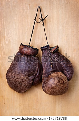 old boxing gloves hang on nail on wall - stock photo