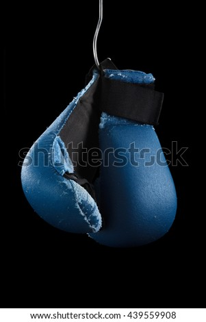 Old boxing or karate gloves hang on nail, black background. Retirement concept - stock photo