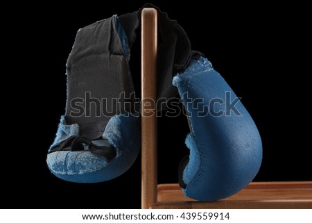 Old boxing or karate gloves hang on the bench, black background. Retirement concept - stock photo