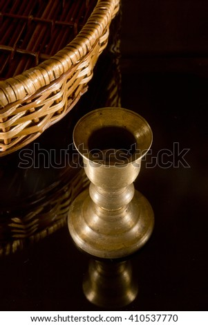 Old brass candlestick on black mirror background