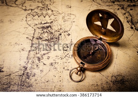 old brass compass on wood table top view