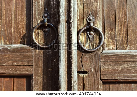 Old brass door handles in the form of ring at the wooden weathered door with keyhole. Architectural background. Vintage filter applied.  - stock photo