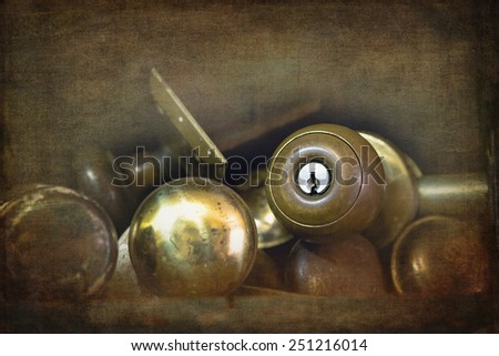 Old brass door knobs discarded on a shelf in a workshop. Textured and filtered to look like an old faded photograph. - stock photo