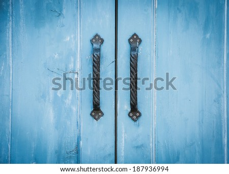 Old brass handle on vintage old blue wood door. - stock photo