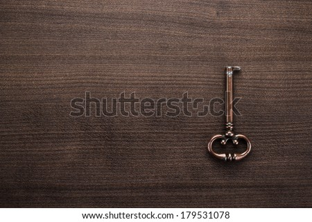 old brass key on the wooden table - stock photo