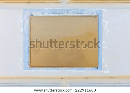 Old brass yellow metal plate framed and nailed on white stone wall background - stock photo