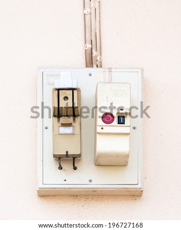 Old breaker box on the wall of urban house. - stock photo
