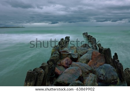 Old breakwater protecting the Baltic coast during a storm in a long exposure.