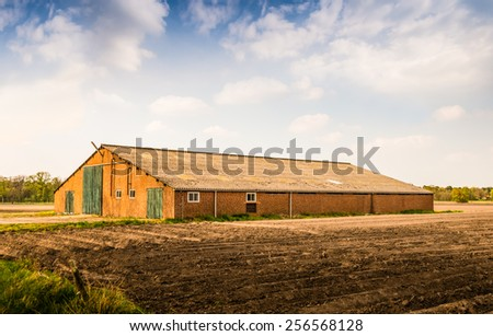 Old brick barn with a corrugated roof and green painted wooden doors. In the foreground a field with the ridges of newly sown potatoes. - stock photo