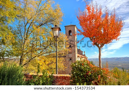 Old brick bell tower as seen among trees with red and yellow leaves in small italian town in autumn. - stock photo