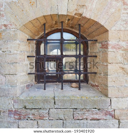 Old brick castle's wall fragment with the caged window as a background texture - stock photo