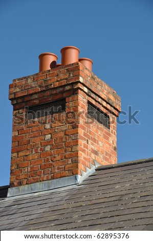 old brick chimney on black tile roof (blue sky) - stock photo
