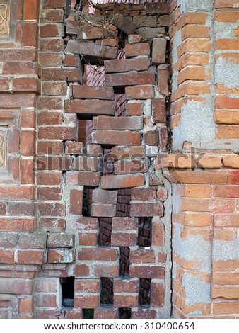 Old brick fence between the houses very carelessly composed        - stock photo