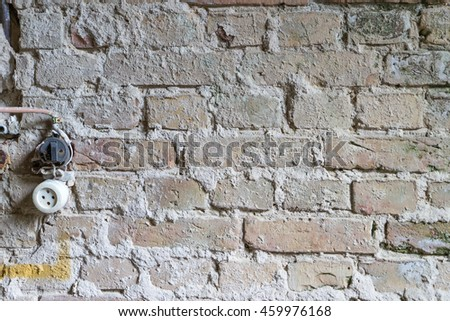 old brick wall and an electrical outlet