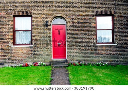Old brick wall and red door in England - stock photo