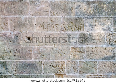 Old brick wall background with Greek graffiti carved into it.