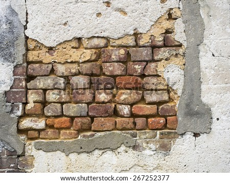 Old brick wall exposed under decaying stucco in Charleston, South Carolina
