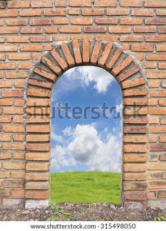 Old brick wall open to green field and blue sky with white clouds. - stock photo