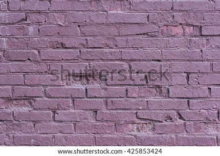 Old brick wall painted in purple. - stock photo
