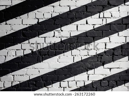 Old brick wall roughly painted black and white - stock photo