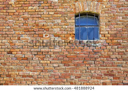 Old brick wall with a small window.