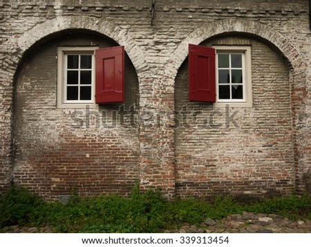 Old brick wall with arches and windows with red wooden blinds - stock photo