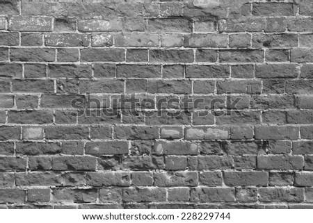 Old brick wall with dark bricks - stock photo