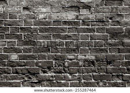 Old brick wall with dark bricks - stock photo