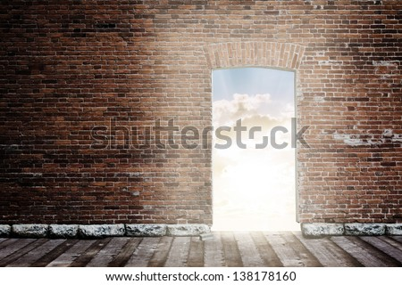old brick wall with opened door to sunset sky - stock photo