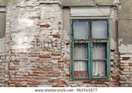 Old bricked up window on a broken derelict ruin house