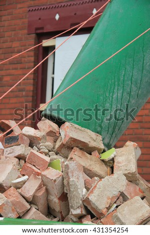 Old bricks and a waste chute near a dumpster - stock photo