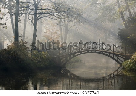 Old bridge in misty autumn park