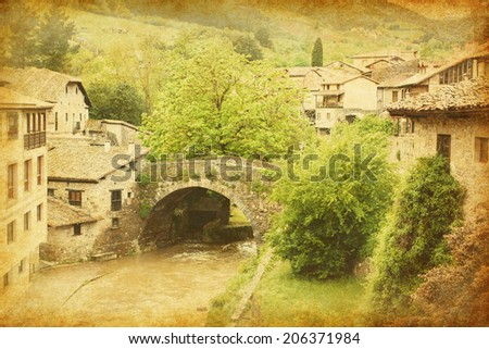 Old  bridge in Potes, Spain. Photo in retro style. Added paper texture